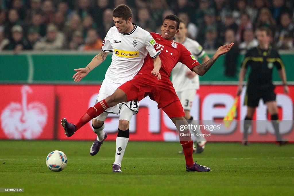 Luiz Gustavo of Bayern challenges Roman Neustaedter of Moenchengladbach during the DFB Cup semi final match between Borussia Moenchengladbach and FC...