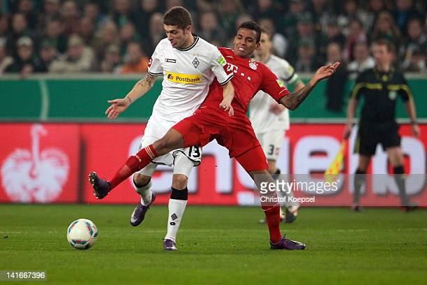 Luiz Gustavo of Bayern challenges Roman Neustaedter of Moenchengladbach during the DFB Cup semi final match between Borussia Moenchengladbach and FC...