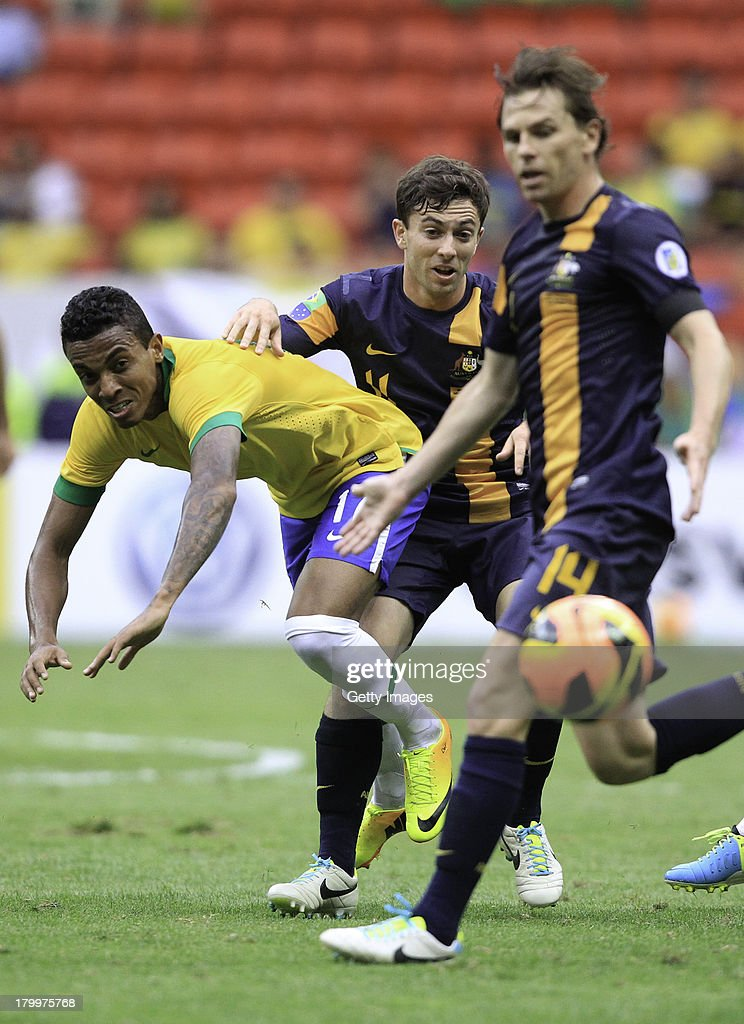 Luiz Gustavo of Brazil fights for the ball with Tommy Oar and Brett Holman of Australia during the International friendly between Brazil and...