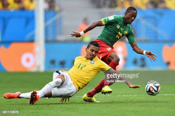 Luiz Gustavo of Brazil is challenged by Enoh Eyong of Cameroon during the 2014 FIFA World Cup Brazil Group A match between Cameroon and Brazil at...
