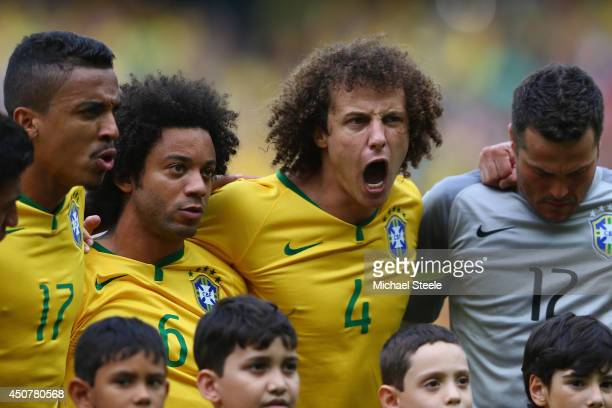 R Luiz Gustavo of Brazil Marcelo David Luiz and Julio Cesar during the national anthems ahead of the 2014 FIFA World Cup Brazil Group A match between...