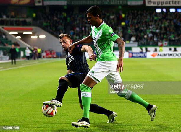 Luiz Gustavo of VfL Wolfsburg and Xherdan Shaqiri of Milano battle for the ball during the UEFA Europa League Round of 16 first leg match between VfL...
