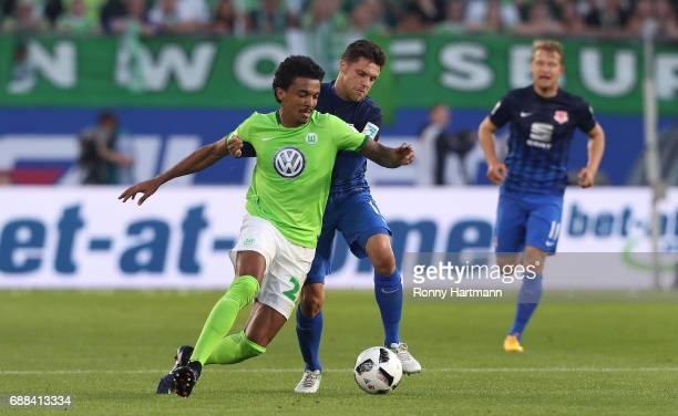 Luiz Gustavo of Wolfsburg competes with Mirko Boland of Braunschweig during the Bundesliga Playoff first leg match between VfL Wolfsburg and...
