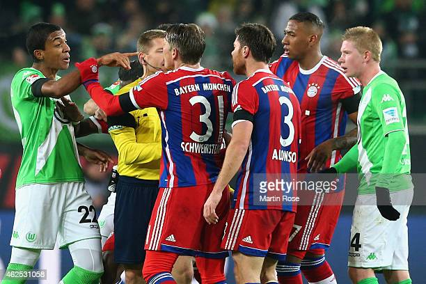 Luiz Gustavo of Wolfsburg discusses with Bastian Schweinsteiger Xabi Alonso and Jerome Boateng of Muenchen during the Bundesliga match between VfL...