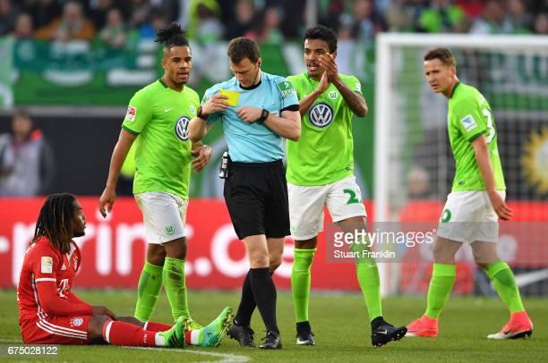 Luiz Gustavo of Wolfsburg gestures to Referee Felix Zwayer after being shown the red card during the Bundesliga match between VfL Wolfsburg and...