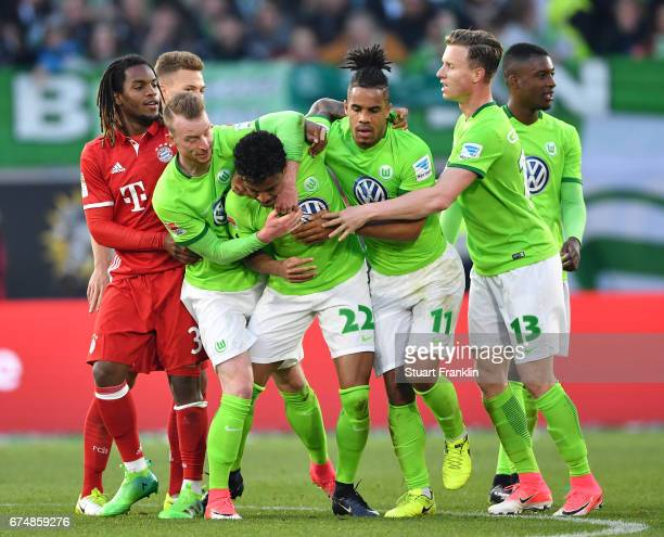 Luiz Gustavo of Wolfsburg is restranded by teamates after being shown the red card during the Bundesliga match between VfL Wolfsburg and Bayern...