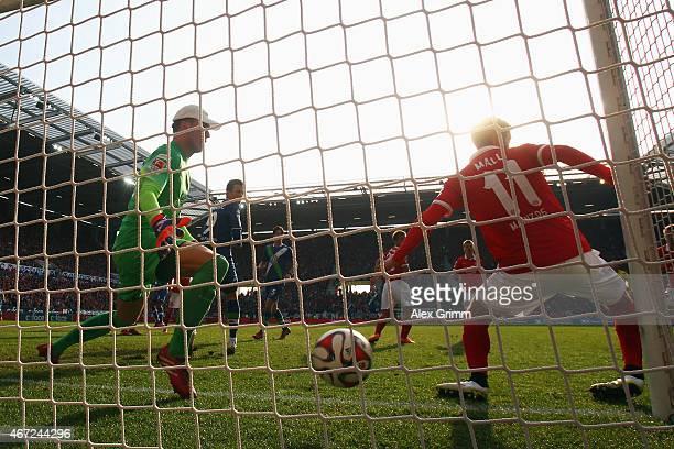 Luiz Gustavo of Wolfsburg scores his team's first goal against goalkeeper Lorius Karius and Yunus Malli of Mainz during the Bundesliga match between...