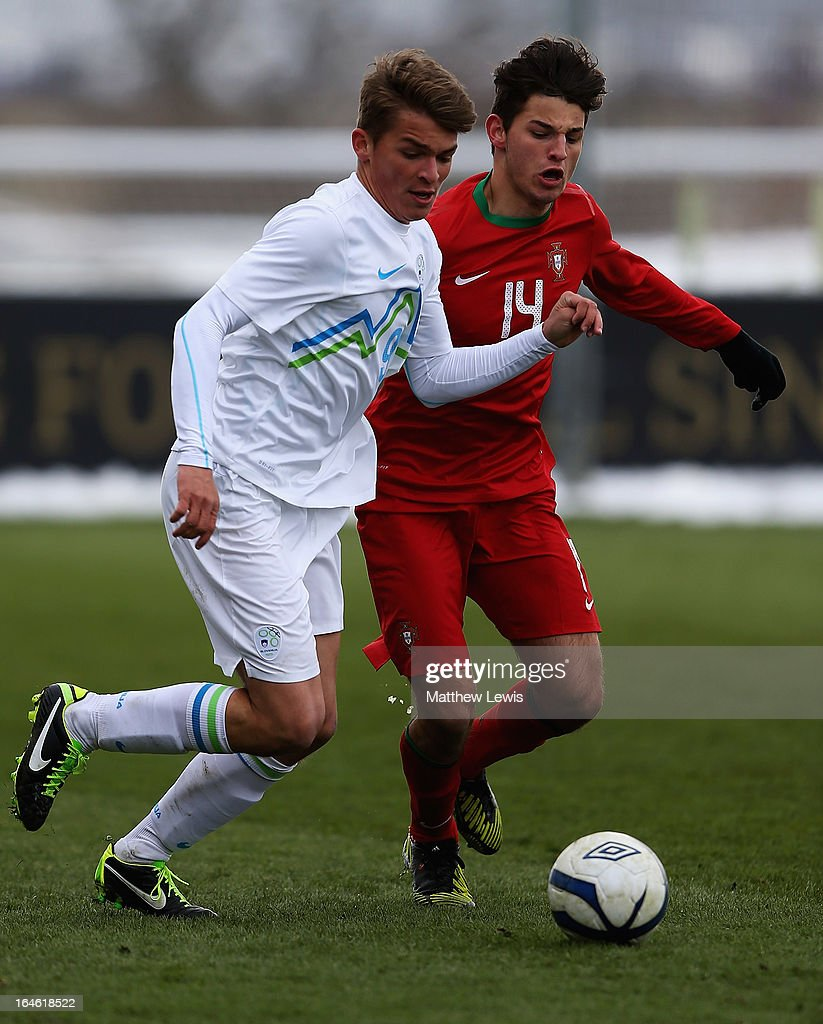 Luka Gajic of Slovenia and Jose Ze Gomes of Portugal challenge for the ball during the UEFA European Under-17 Championship Elite Round match between Slovenia and Portugal at St George's Park on March 25, 2013 in Burton-upon-Trent, England.