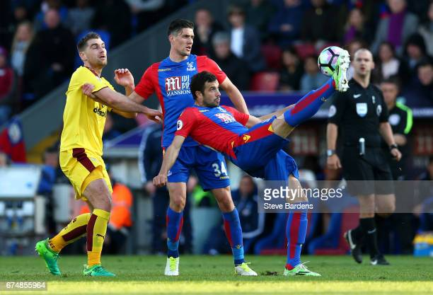 Luka Milivojevic of Crystal Palace clears with Sam Vokes of Burnley and Martin Kelly of Crystal Palace during the Premier League match between...