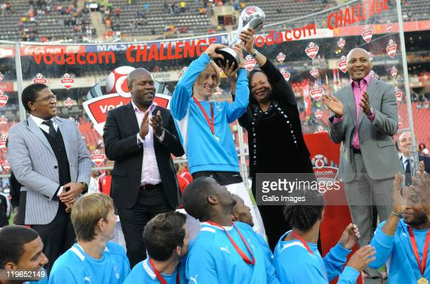 Luka Modric and Tottenham teammates celebrate with the trophy joined by South Africa's Minister of Sport Fikile Mbalula and Lebohang Maile after the...