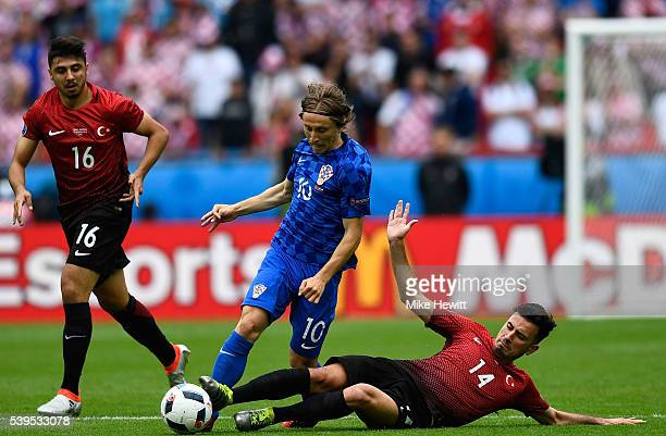 Luka Modric of Croatia is tackled by Oguzhan Ozyakup of Turkey during the UEFA EURO 2016 Group D match between Turkey and Croatia at Parc des Princes...