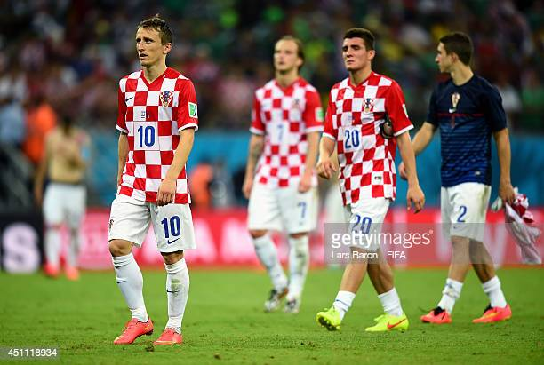 Luka Modric of Croatia walks off the pitch dejected with teammates after losing the 2014 FIFA World Cup Brazil Group A match between Croatia and...