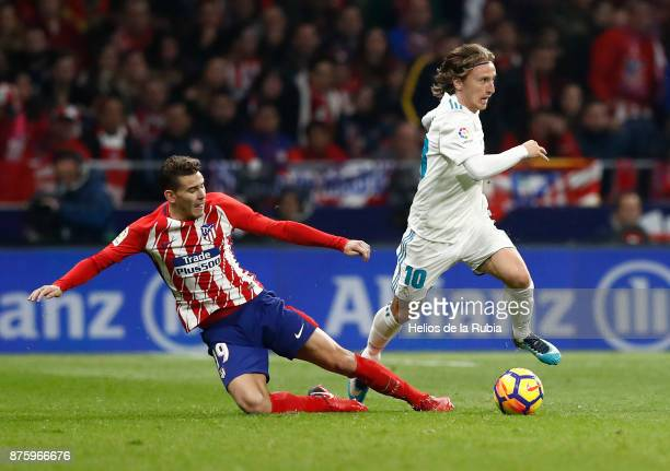 Luka Modric of Real Madrid and Lucas Hernndez of Atletico de Madrid compete for the ball during the La Liga match between Atletico Madrid and Real...