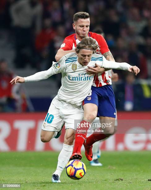 Luka Modric of Real Madrid and Sal guez of Atletico de Madrid compete for the ball during the La Liga match between Atletico Madrid and Real Madrid...