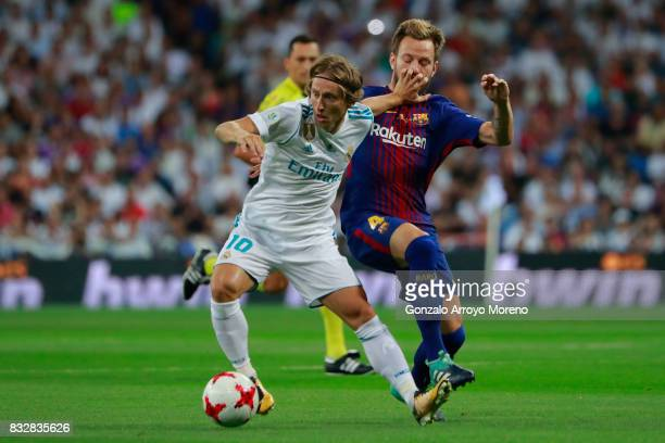 Luka Modric of Real Madrid CF competes for the ball with Ivan Rakitic of FC Barcelona during the Supercopa de Espana Final 2nd Leg match between Real...