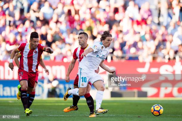 Luka Modric of Real Madrid CF conducts the ball past Francisco Aday and Borja Garcia of Girona FC during the La Liga match between Girona and Real...