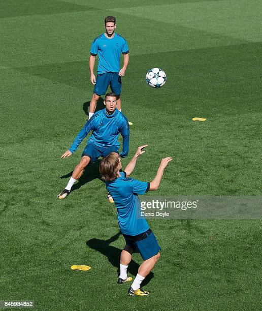 Luka Modric of Real Madrid CF controls the ball beside Cristiano Ronaldo and Marco Asensio during the Real Madrid CF training session at Valdebebas...
