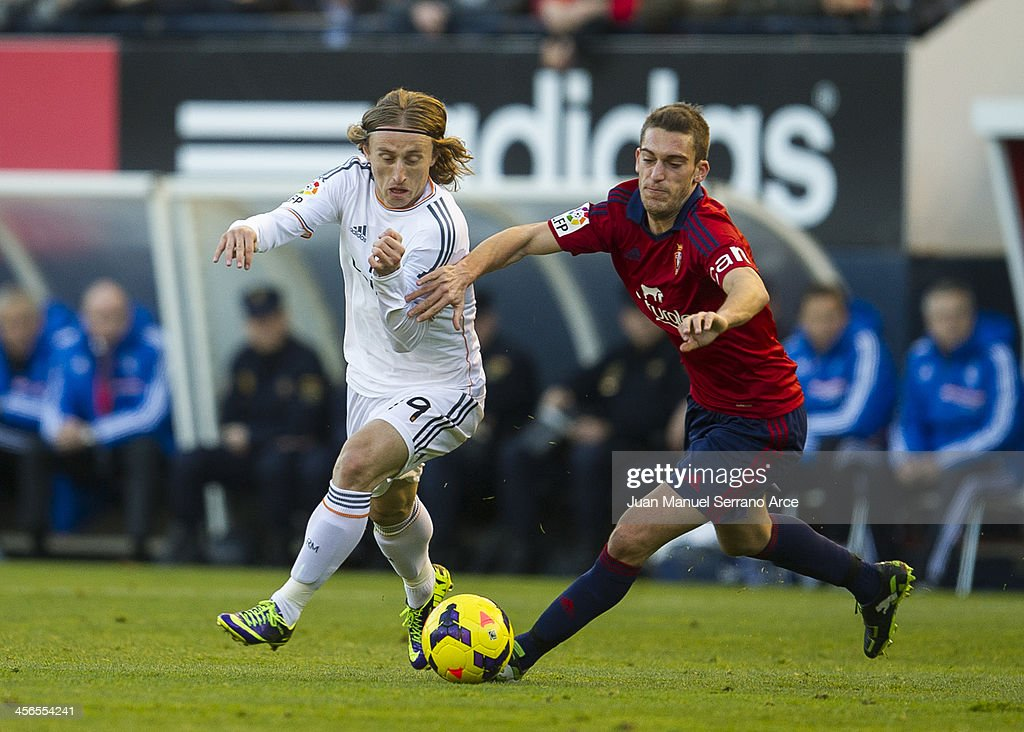 <a gi-track='captionPersonalityLinkClicked' href=/galleries/search?phrase=Luka+Modric&family=editorial&specificpeople=560350 ng-click='$event.stopPropagation()'>Luka Modric</a> of Real Madrid CF duels for the ball with Roberto Torres of CA Osasuna during the La Liga match between CA Osasuna and Real Madrid CF at Estadio Reyno de Navarra on December 14, 2013 in Pamplona, Spain.