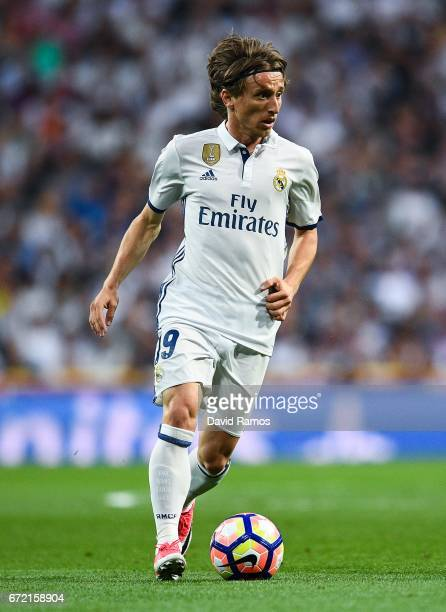 Luka Modric of Real Madrid CF runs with the ball during the La Liga match between Real Madrid CF and FC Barcelona at the Santiago Bernabeu stadium on...