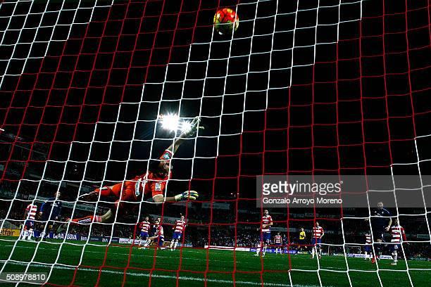 Luka Modric of Real Madrid CF scores their opening goal against goalkeeper Andres Fernandez of Granada CF during the La Liga match between Granada CF...