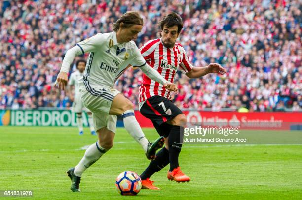 Luka Modric of Real Madrid competes for the ball with Benat Etxebarria of Athletic Club during the La Liga match between Athletic Club Bilbao and...