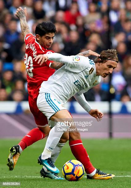 Luka Modric of Real Madrid competes for the ball with Ever Banega of Sevilla during the La Liga match between Real Madrid and Sevilla at Estadio...