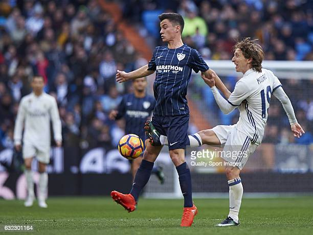Luka Modric of Real Madrid competes for the ball with Juan Pablo Anor of Malaga during the La Liga match between Real Madrid CF and Malaga CF at...