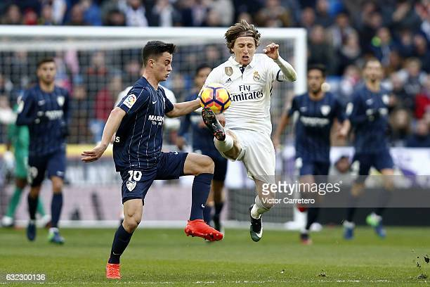 Luka Modric of Real Madrid competes for the ball with Juanpi of Malaga during the La Liga match between Real Madrid and Malaga CF at Estadio Santiago...