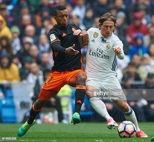 Luka Modric of Real Madrid competes for the ball with Nani of Valencia during the La Liga match between Real Madrid CF and Valencia CF at Estadio...