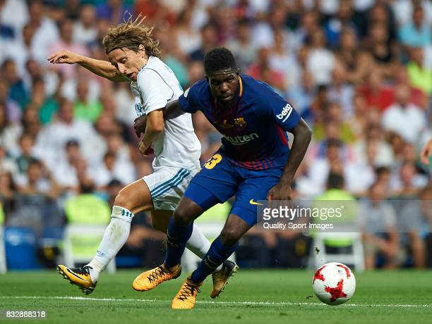 Luka Modric of Real Madrid competes for the ball with Samuel Umtiti of Barcelona during the Supercopa de Espana Supercopa Final 2nd Leg match between...