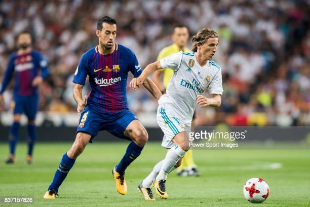 MADRID SPAIN AUGUST 16 Luka Modric of Real Madrid competes for the ball with Sergio Busquets Burgos of FC Barcelona during their Supercopa de Espana...