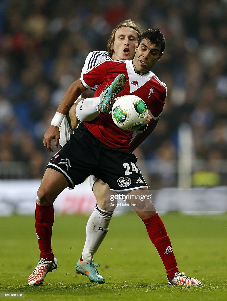 Luka Modric of Real Madrid duels for the ball with Augusto Fernandez of Celta de Vigo during the round of 16 Copa del Rey second leg match between Real Madrid and Celta de Vigo at Estadio Santiago Bernabeu on January 9, 2013 in Madrid, Spain.