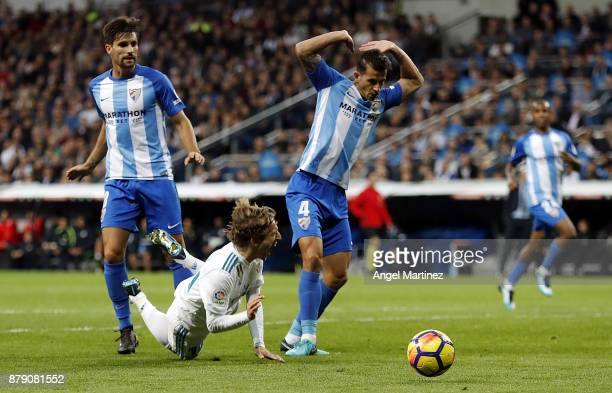 Luka Modric of Real Madrid falls in the penalty area during the La Liga match between Real Madrid and Malaga at Estadio Santiago Bernabeu on November...