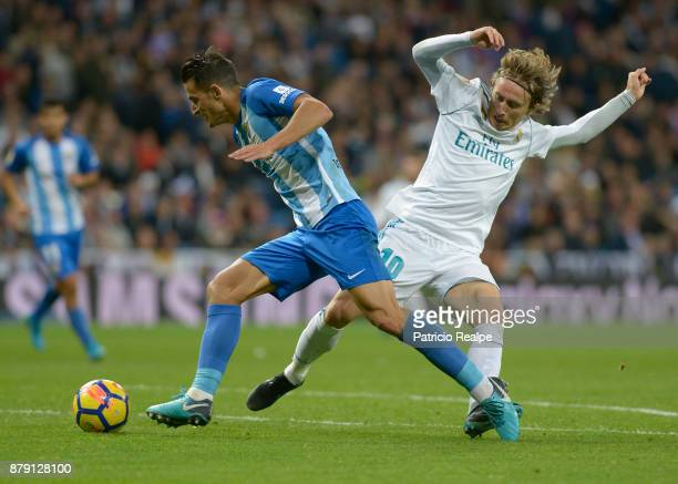 Luka Modric of Real Madrid figths for the ball with Diego Glez of Malaga during a match between Real Madrid and Malaga as part of La Liga at Santiago...