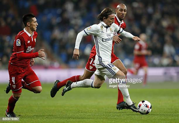 Luka Modric of Real Madrid is chased by Steven NÕZonzi and Matias Kranevitter of Sevilla during the Copa del Rey round of 16 first leg match between...