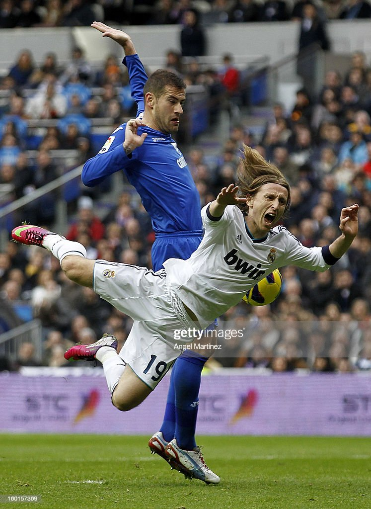 <a gi-track='captionPersonalityLinkClicked' href=/galleries/search?phrase=Luka+Modric&family=editorial&specificpeople=560350 ng-click='$event.stopPropagation()'>Luka Modric</a> of Real Madrid is tackled by Lopo Garcia of Getafe during the La Liga match between Real Madrid an Getafe at Estadio Santiago Bernabeu on January 27, 2013 in Madrid, Spain.
