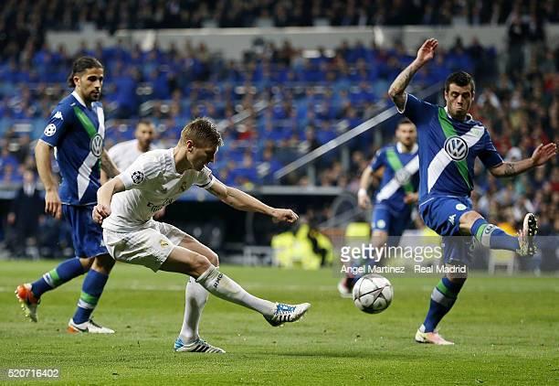 Luka Modric of Real Madrid shoots on goal past Vieirinha of VfL Wolfsburg during the UEFA Champions League quarter final second leg match between...