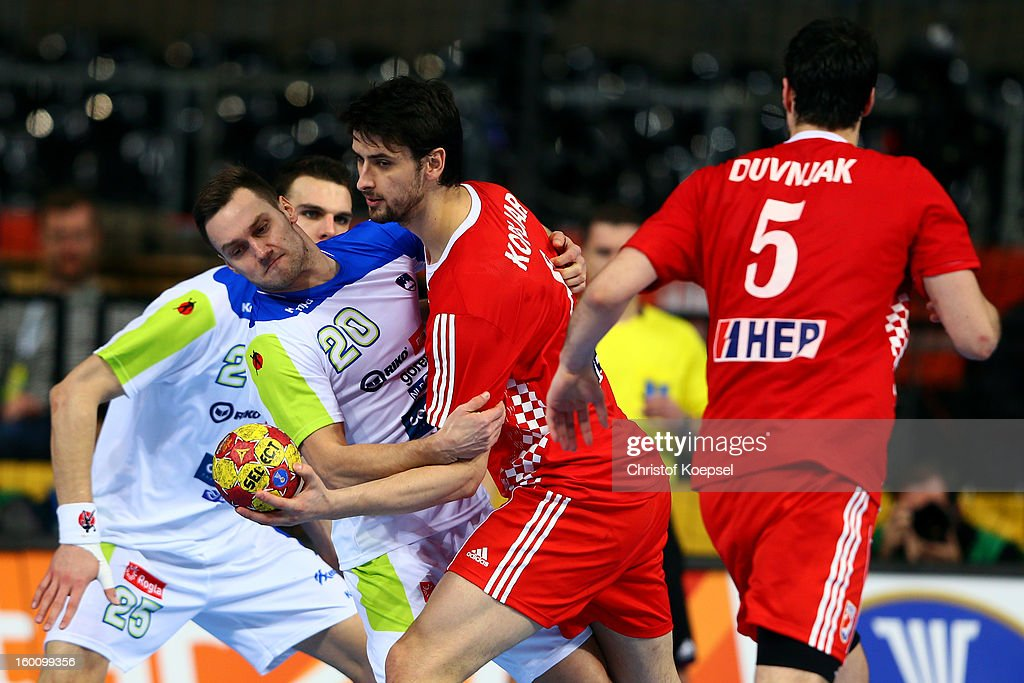 Luka Zvizej of Slovenia (L) defends against Marko Kopljar of Croatia (C) during the Men's Handball World Championship 2013 third place match between Slovenia and Croatia at Palau Sant Jordi on January 26, 2013 in Barcelona, Spain.