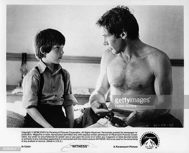 Lukas Haas talks with Harrison Ford in a scene from the Paramount Pictures movie 'Witness' circa 1985