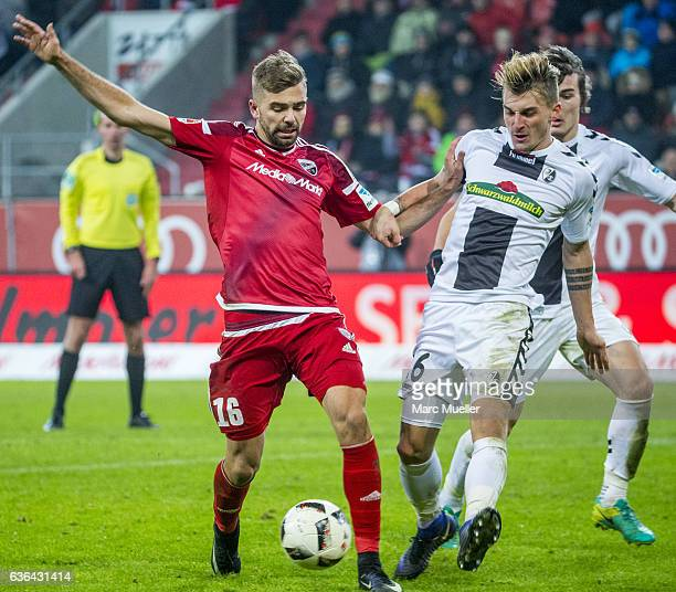 Lukas Hinterseer of FC Ingolstadt 04 is challenged by Amir Abrashi of SC Freiburg during the Bundesliga match between FC Ingolstadt 04 and SC...