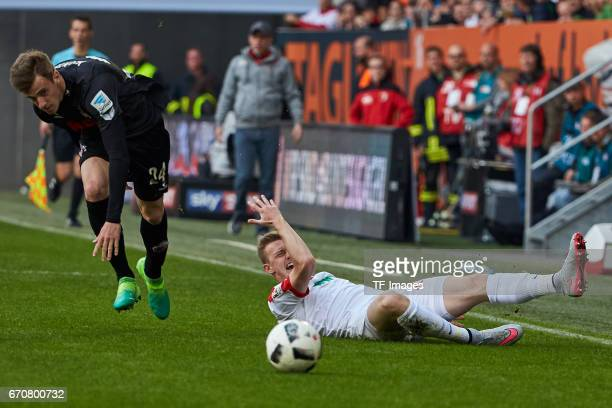 Lukas Kluenter and Georg Teigl battle for the ball during the Bundesliga match between FC Augsburg and 1 FC Koeln at WWK Arena on April 15 2017 in...
