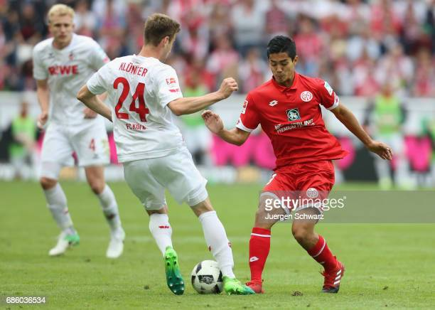 Lukas Kluenter of Cologne and Yoshinori Muto of Mainz fight for the ball during the Bundesliga match between 1 FC Koeln and 1 FSV Mainz 05 at...