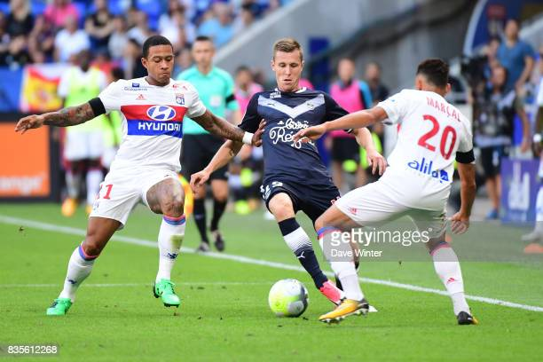 Lukas Lerager of Bordeaux tries to slip the ball between Memphis Depay of Lyon and Fernando Marcal of Lyon during the Ligue 1 match between Olympique...