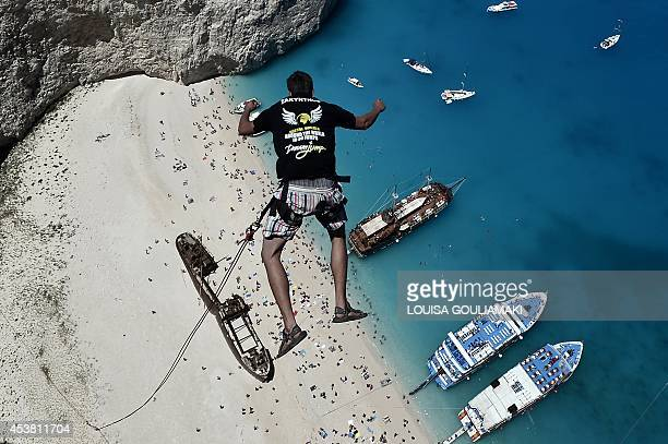 Lukas Michul a member of the 'dream walker' group jumps from atop the rugged rocks overlooking the azure waters of Navagio beach one of the Greece's...