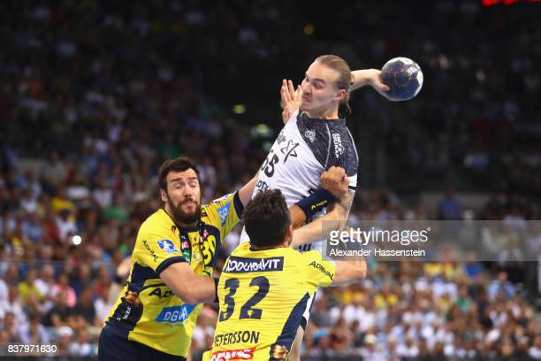 Lukas Nilsson of Kiel battles for the ball with Alexander Petersson of RheinNeckar Loewen and his team mate Gedeon Guardiola Villaplana during the...