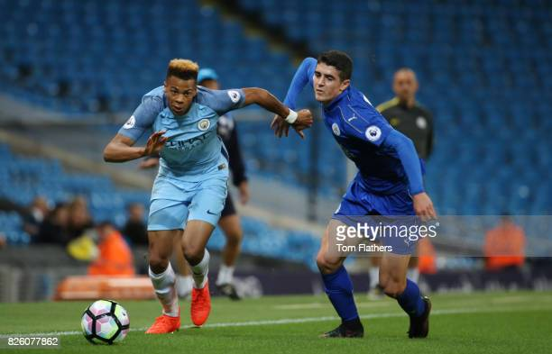 Lukas Nmecha of Manchester City is challenged by Alex Pascanu of Leicester City