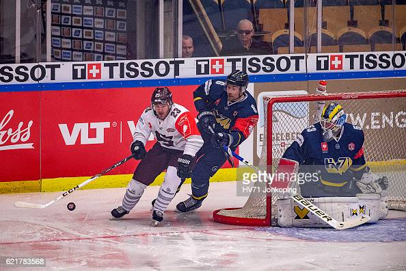 Lukas Pech of Sparta Prague passing behind Fredrik PetterssonWentzel goaltender of HV71 and chased by Cristoffer Persson of HV71 during the Champions...