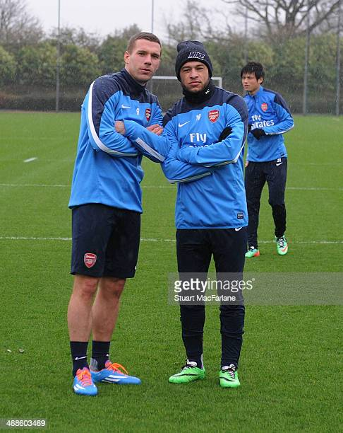 Lukas Podolski and Alex OxladeChamberlain of Arsenal before a training session at London Colney on February 11 2014 in St Albans England