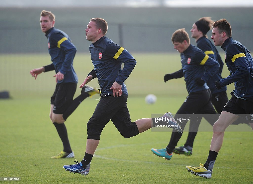 Lukas Podolski (C) and Arsenal team-mates warm up during a training session ahead of their UEFA Champions League round of 16 first leg match against FC Bayern Muenchen at London Colney on February 18, 2013 in St Albans, England.