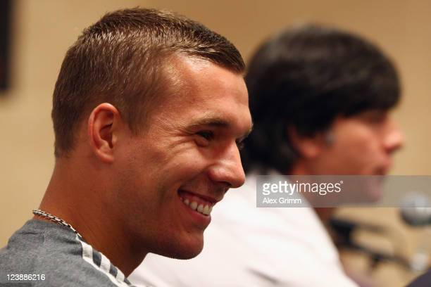 Lukas Podolski and head coach Joachim Loew attend a Germany press conference ahead of their friendly match against Poland at Baltic Arena on...